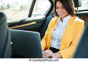 Businesswoman sitting on back seat of car and working