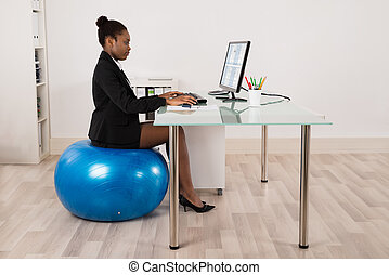 Businesswoman Sitting On Fitness Ball In Office