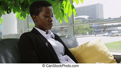 Businesswoman sitting on sofa and using laptop in office 4k...