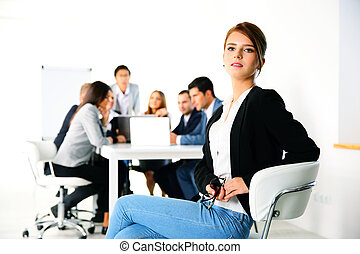 Businesswoman sitting on the office chair in front of business meeting