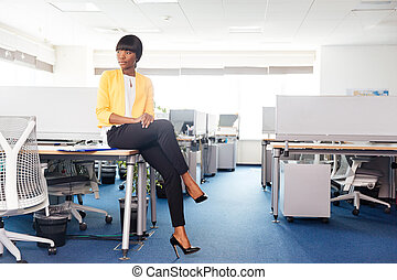 Businesswoman sitting on the table in office