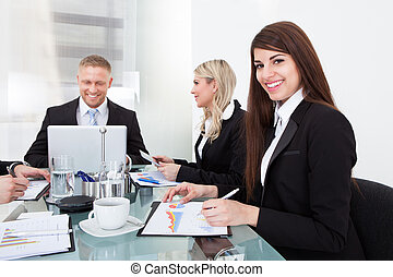 Businesswoman Sitting With Colleagues In Meeting