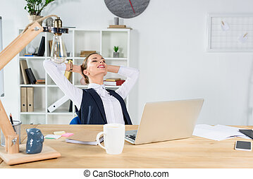 businesswoman sitting with hands behind head