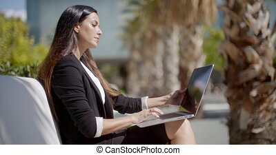 Businesswoman sitting working in an urban park