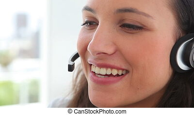 Businesswoman smiles as she talks on a headset