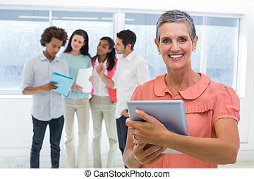 Businesswoman smiles at camera while looking at tablet pc with coworkers behind her in the office