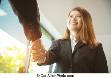 Businesswoman smiling and shaking hand with businessman