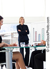 Businesswoman smiling at her team in a presentation