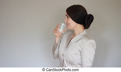 Businesswoman smiling, looking at camera and drinking glass water. Elegant brunette woman in a suit