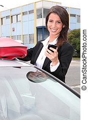 Businesswoman smiling on the phone next to her car