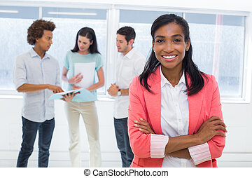 Businesswoman smiling to camera with colleagues in...