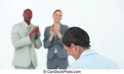 Businesswoman smiling while her colleagues are congratulating her
