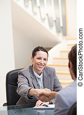 Businesswoman smiling while shaking hands