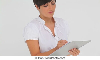 Businesswoman smiling while writing on a clipboard