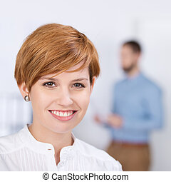 Closeup portrait of businesswoman smiling with coworker in background at office