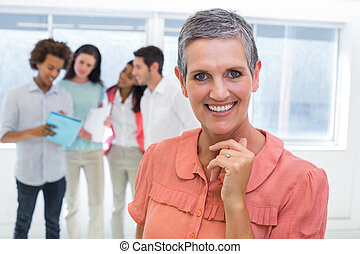 Businesswoman smiling with coworkers behind working