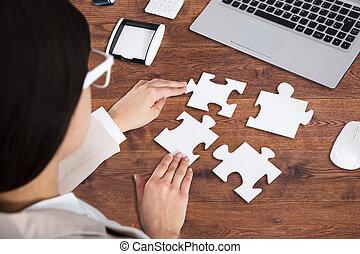 Businesswoman Solving Jigsaw Puzzle