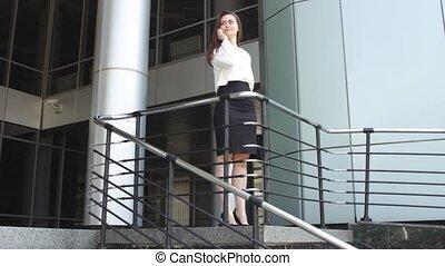 Businesswoman speaking on phone near railing - Attractive...