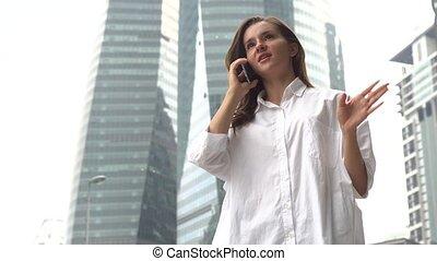 Businesswoman speaks on mobile phone.