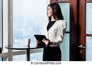 Businesswoman standing at skyscraper window with skyline view