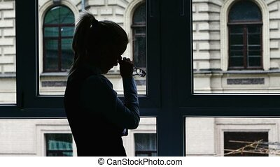Businesswoman standing at the window after a busy day. Feels tired, headache. Silhouette.