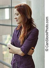 businesswoman standing at window smling - looking down on creation