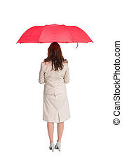 Businesswoman standing back to camera holding red umbrella