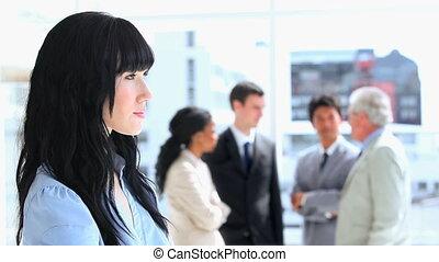 Businesswoman standing in front of her work team