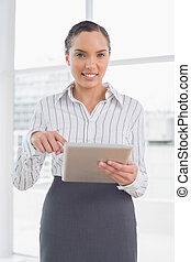 Businesswoman standing in her office and pointing at tablet screen while looking at camera
