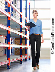Businesswoman standing in next to shelves in warehouse with clipboard