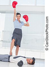 Businesswoman standing on defeated businessman wearing...