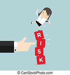 Businesswoman standing on shaky risk blocks by hand of manager.