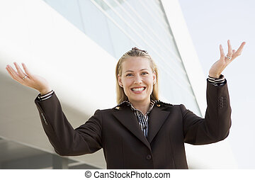 Businesswoman standing outdoors by building smiling with hands o