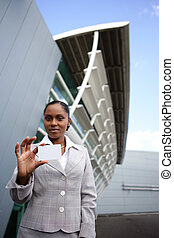 Businesswoman standing outside and holding her business card