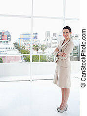 Businesswoman standing upright in front of the bright window