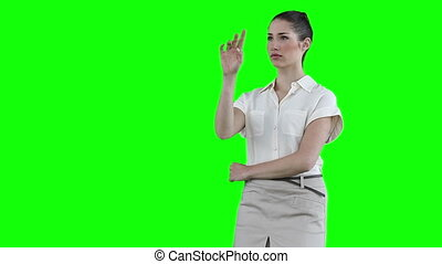 Businesswoman standing while using a virtual touchscreen