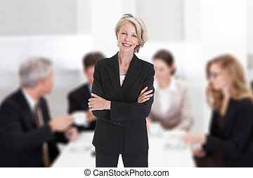 Businesswoman Standing With Arms Crossed In Boardroom