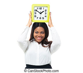 Businesswoman standing with clock on head