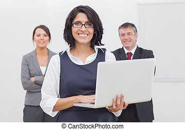 Businesswoman standing with laptop