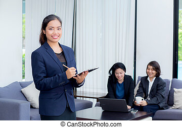 businesswoman standing with notebook with colleagues in team on background.