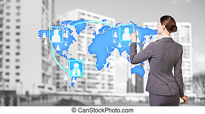 Businesswoman stands near map with icons