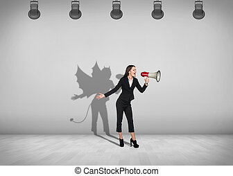 Businesswoman stands with shadow on the wall