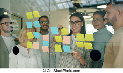 Businesswoman sticking notes on glassboard discussing ideas ...