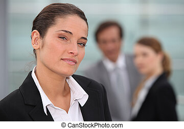 Businesswoman stood with colleagues in background