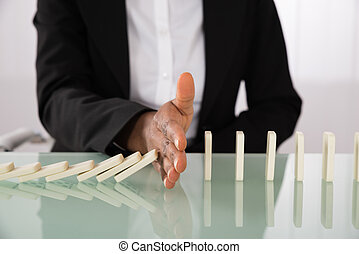 Businesswoman Stopping Dominoes From Falling