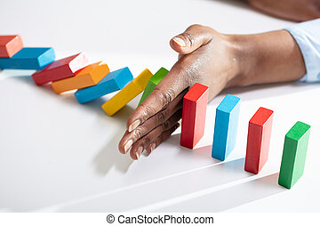 Close-up Of A Businesswoman Hand Stopping Colorful Dominoes From Falling On Office Desk