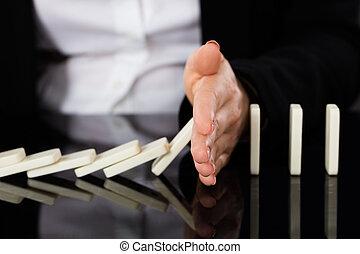 Businesswoman Stopping Dominoes On Desk