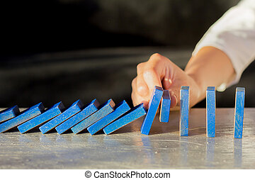 Businesswoman Stopping The Effect Of Domino With Hand At Desk