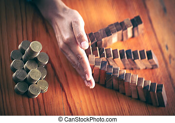 Businesswoman stops the domino effect from risking financial investment, concept image of investing and banking.