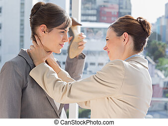 Businesswoman strangling another